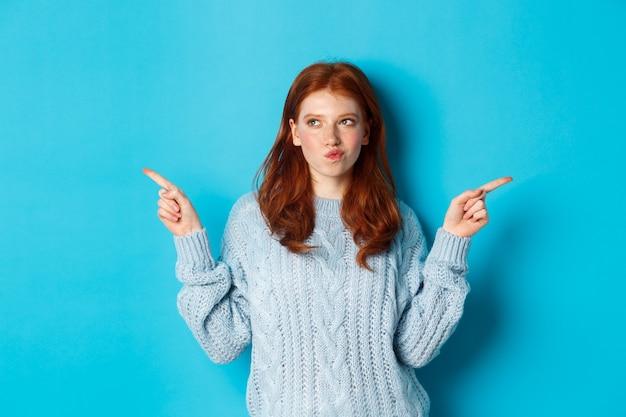 겨울 방학 및 사람들 개념. 사려 깊은 빨간 머리 소녀 결정을 내리고, 손가락을 옆으로 가리키고, 두 가지 방법 중 선택, 파란색 배경 위에 서
