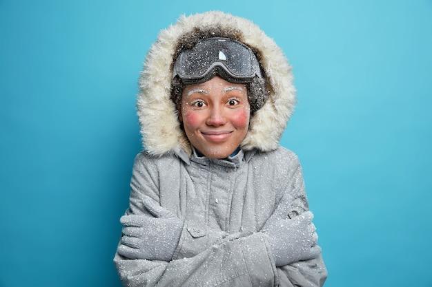겨울 방학 및 레크리에이션 개념. 쾌활한 냉동 여성은 산에서 스노우 보드를 갔다가 추위를 느끼고 떨며 따뜻하게 자신을 포옹하고 후드 장갑이 달린 회색 재킷을 입고 만족감을 느낍니다.