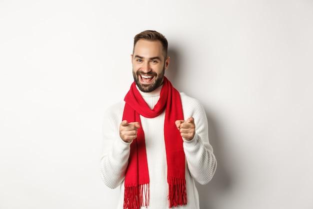 겨울 휴가 및 쇼핑 개념입니다. 흰색 배경 위에 서서 행복한 크리스마스를 기원하며 칭찬하거나 축하하기 위해 손가락을 가리키는 수염 난 남자
