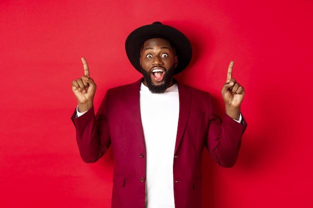 冬の休日とショッピングのコンセプト。指を上に向け、ロゴを表示し、幸せな赤い背景に笑みを浮かべて、パーティー衣装で陽気なアフリカ系アメリカ人の男。