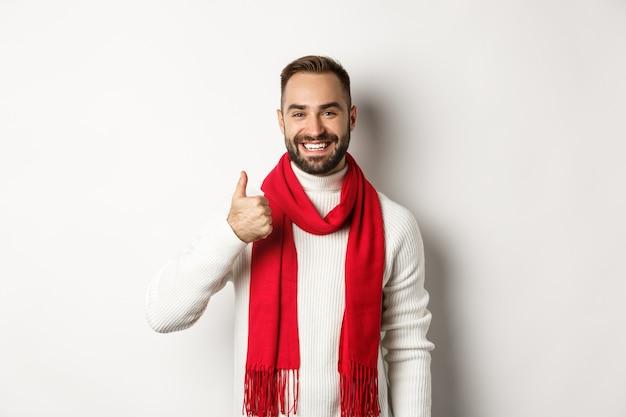 겨울 휴가 및 쇼핑 개념입니다. 흰색 바탕에 크리스마스 스웨터와 빨간 스카프를 두르고 엄지손가락을 치켜드는 자신감 있는 잘생긴 남자.
