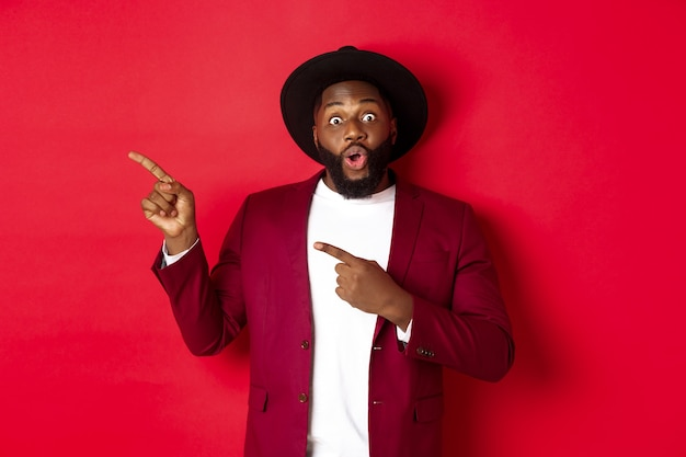겨울 휴가 및 쇼핑 개념입니다. 왼쪽을 가리키며 웃고 있는 행복한 흑인 남자는 빨간색 배경에 새해 프로모션 제안을 보여줍니다.