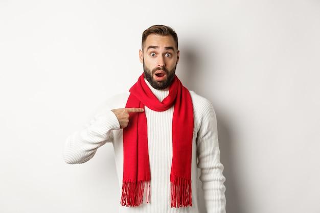 겨울 휴가 및 쇼핑 개념입니다. 흰색 배경에 빨간색 스카프와 스웨터를 입고 자신을 가리키며 선택받고 있는 놀라고 혼란스러운 남자