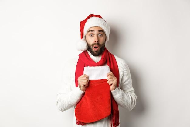 冬の休日とショッピングのコンセプト。クリスマスの靴下で贈り物を受け取っているサンタの帽子の驚いた男、驚いて見える、白い背景に立って