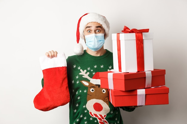 冬の休日とクリスマスのコンセプト。フェイスマスクとサンタ帽子の幸せな男は、贈り物を持って、クリスマスの靴下とプレゼントの箱を持って、白い背景の上に立っています。