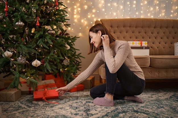 겨울 방학, 축하 및 사람들이 개념-가까운 크리스마스 트리 아래 선물 퍼팅 여자의 최대