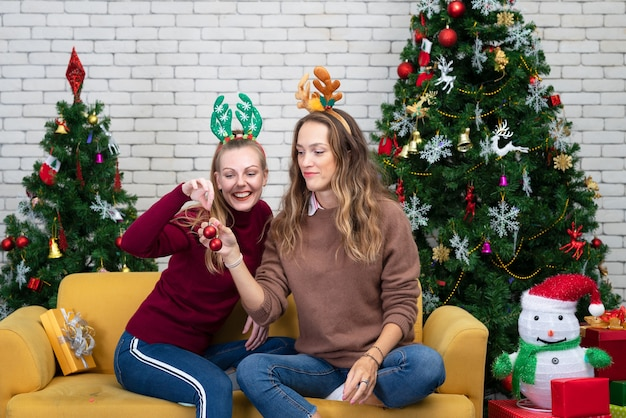 冬の休日、お祝い、人々のコンセプト。ボールでクリスマスツリーを飾る女性 Premium写真