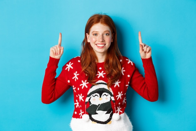 Winter holidays and celebration concept. cute redhead girl in christmas sweater, smiling and pointing fingers up at promo logo, standing over blue background.