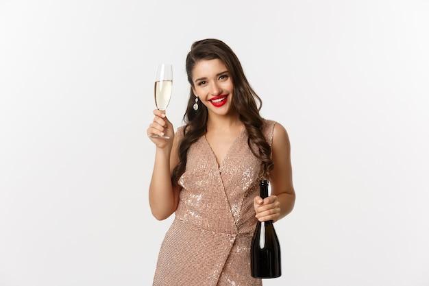 Концепция празднования зимних праздников. счастливая женщина на новогодней вечеринке в роскошном платье, пьет шампанское и улыбается, стоя на белом фоне