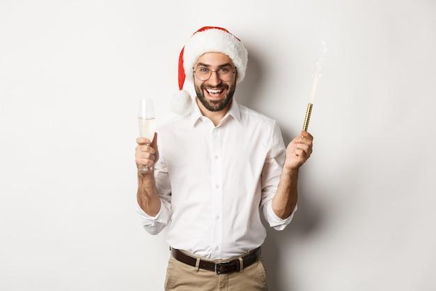 Vacanze invernali e celebrazione. uomo barbuto bello che ha festa di capodanno, con scintilla di fuochi d'artificio e champagne, indossando il cappello della santa