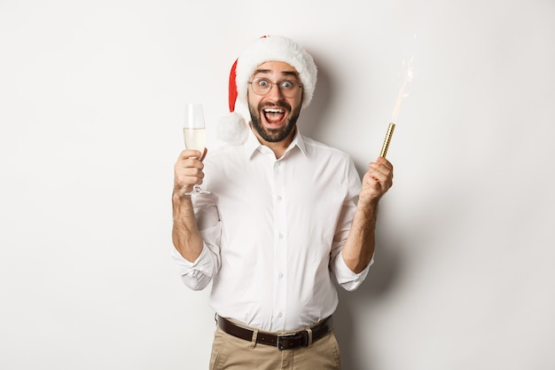 Winter holidays and celebration. handsome bearded man having new year party, holding firework sparkler and champagne, wearing santa hat, white background.