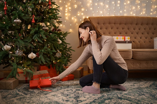 Winter holidays, celebration and people concept - close up of woman putting present under christmas tree