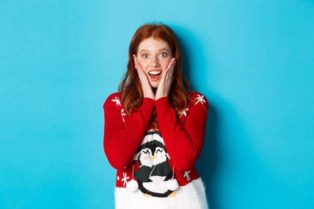 Vacanze invernali e concetto di vigilia di natale. ragazza rossa emozionante in maglione di natale che sembra sorpresa alla macchina fotografica, in piedi su sfondo blu.