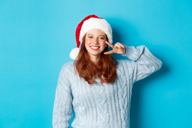 Vacanze invernali e concetto di vigilia di natale. adolescente felice con i capelli rossi, indossando il cappello di babbo natale, godendo il nuovo anno, mostrando il segno di pace e sorridente, in piedi su sfondo blu.