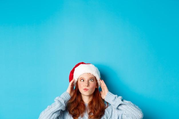 Vacanze invernali e concetto di vigilia di natale. testa di una ragazza rossa divertente con un cappello da babbo natale, appare dal basso e socchiude gli occhi, facendo facce stupide, in piedi vicino allo spazio della copia su sfondo blu