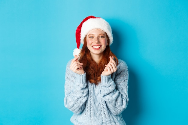Winter holidays and christmas eve concept. hopeful redhead girl in santa hat, making wish on xmas with fingers crossed, wearing santa hat, standing over blue background