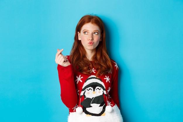 Vacanze invernali e concetto di vigilia di natale. bella donna rossa in maglione natalizio, che mostra il segno del cuore e pensa, guardando l'angolo in alto a sinistra del logo, sfondo blu
