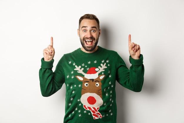 Vacanze invernali e natale. uomo eccitato che punta le dita in alto, mostra pubblicità, in piedi su sfondo bianco
