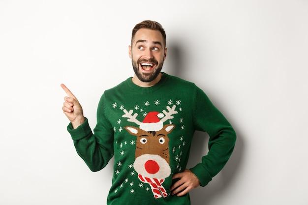 Vacanze invernali e natale. uomo felice in un maglione divertente che punta il dito sul logo nell'angolo in alto a sinistra, che mostra pubblicità, sfondo bianco.