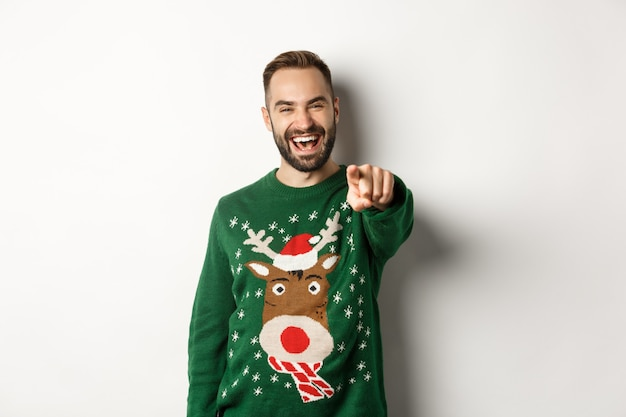 Winter holidays and christmas. happy young man celebrating new year eve, pointing finger at you and laughing, standing over white background