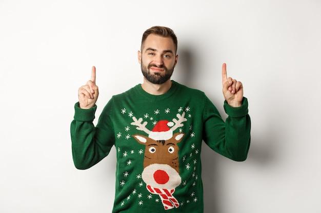 Vacanze invernali e natale. ragazzo barbuto non divertito con un maglione divertente che punta le dita in alto, mostrando qualcosa di sgradevole, sfondo bianco
