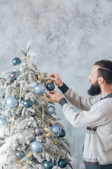 겨울 휴가 개념. 파란색 공 장신구와 전나무 트리를 장식 수염 된 Hipster 남자. 프리미엄 사진