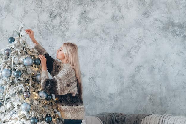 겨울 휴가 개념. 전나무 나무를 장식하는 아늑한 스웨터에 금발 아가씨
