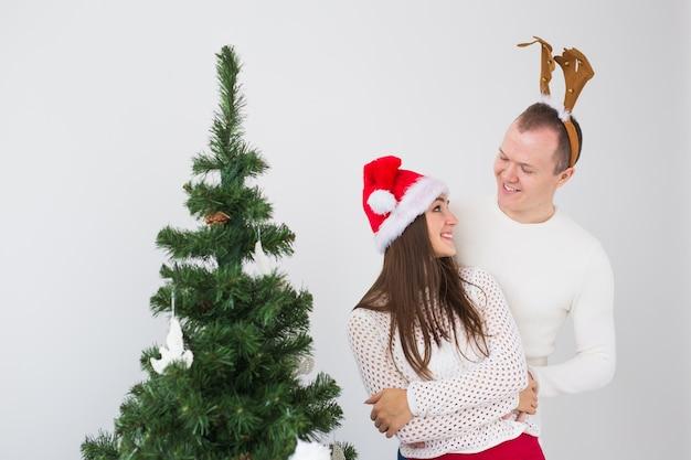冬の休日のコンセプト-サンタの帽子と鹿の角を身に着けているクリスマスのカップル。笑顔の家族