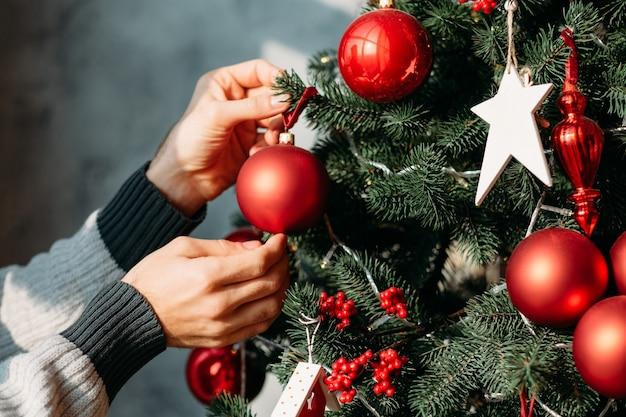 Концепция зимних праздников. человек руки украшая зеленую ель с орнаментом красный шар.