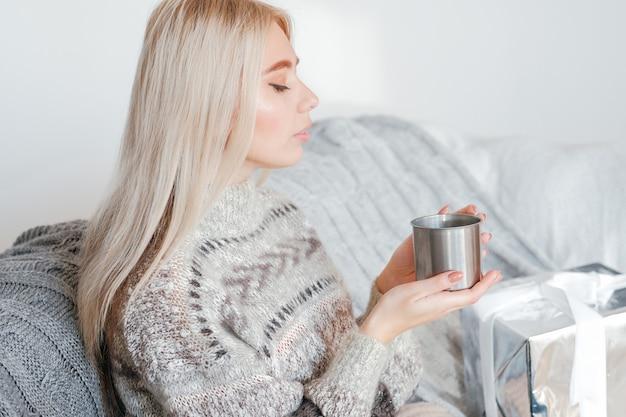 겨울 휴가 개념. 아늑한 스웨터에 평화로운 여자의 초상화, 소파에 앉아 뜨거운 음료를 즐기고
