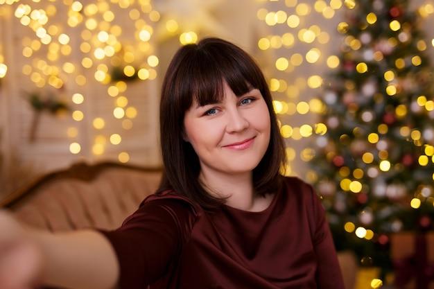 Концепция зимних праздников - молодая красивая женщина, делающая селфи-фото в украшенной гостиной с елкой и праздничными светодиодными огнями