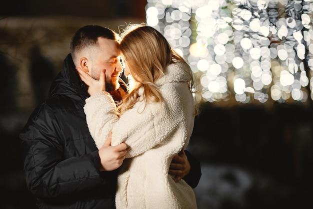 겨울 휴가 개념. 젊은 커플의 야외 야간 초상화입니다. 유럽 도시의 거리에서 포즈.