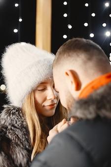 冬の休日の概念。若いカップルの屋外の夜の肖像画。ヨーロッパの街の通りでポーズ。