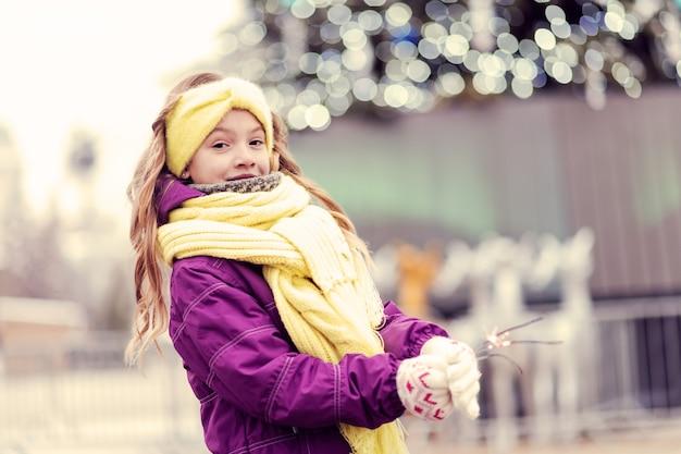겨울 방학. 밖에 서 걷는 동안 세련된 스카프를 착용하는 귀여운 금발 아이