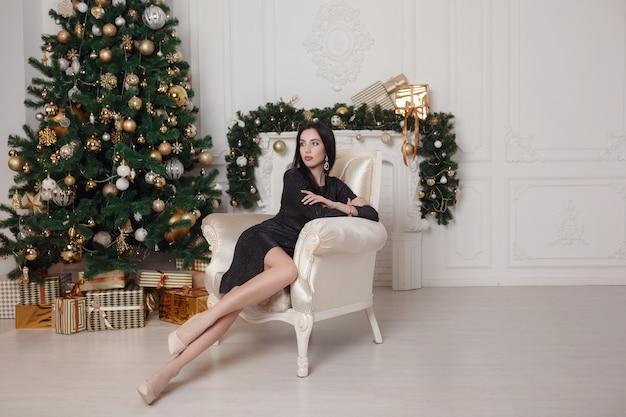 冬の休日の装飾。金持ちの前にプレゼントボックスでポーズをとるドレスの魅力的で幸せな女性