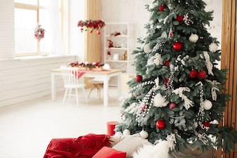 Winter holidays decor. Rich decorated New Year tree stands with present boxes