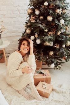 Winter holidays decoration. warm colors. charming brunette woman in beige sweater