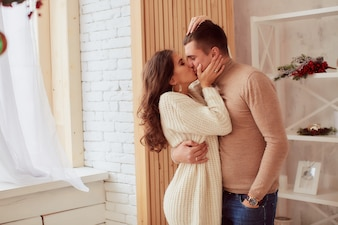Winter holidays decoration. Warm colors. Charming young couple hugs each other tenderly