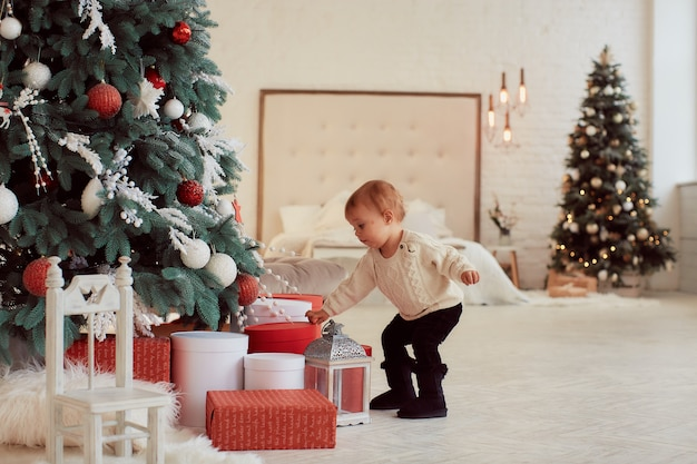 Winter holidays decorations. warm colors. beautiful little girl plays with present boxes