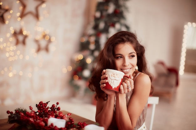 Winter holidays decorations. warm colors. charming brunette woman in beige dress