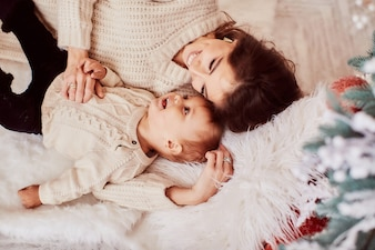 Winter holidays decorations. Warm colors. Family portrait. Mom and little lovely daughter
