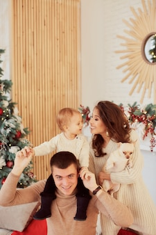 Winter holidays decorations. warm colors. family portrait. mom, dad and their little daughter
