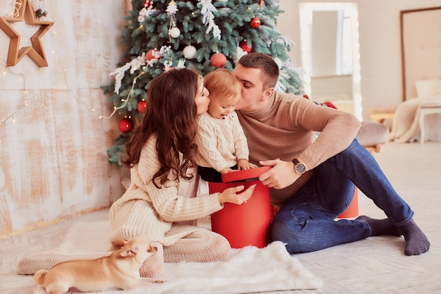 Winter holidays decorations. warm colors. mom, dad and little daughter play with a dog