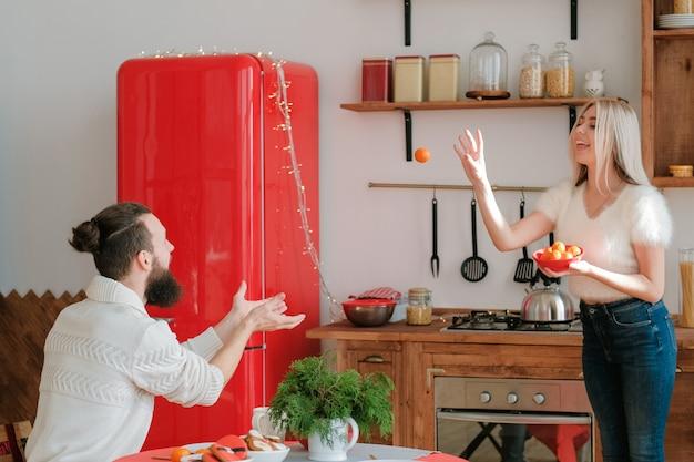 겨울 방학 재미. 현대 부엌에서 관화를 가지고 노는 커플, 그녀의 남자 친구에게 과일을 던지는 아가씨. 프리미엄 사진