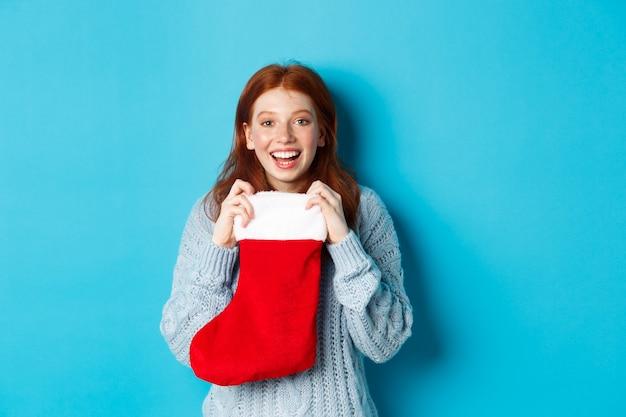 Vacanze invernali e concetto di regali. felice ragazza dai capelli rossi che riceve un regalo di natale, apre la calza di natale e sorride stupita, in piedi su sfondo blu