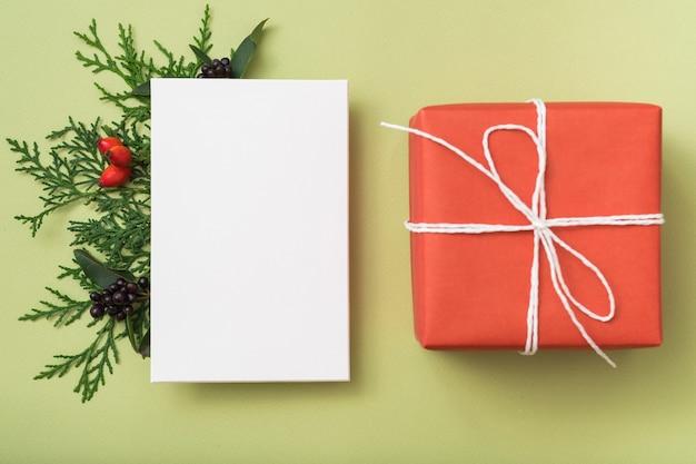 冬休みのご挨拶。白い白紙。ギフト用の箱。ジュニパーの装飾。