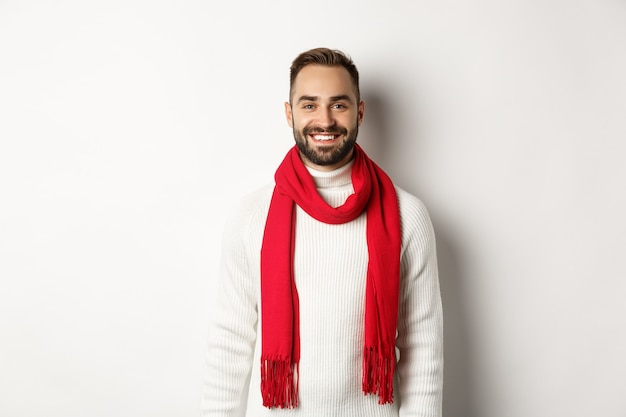 Vacanze invernali. bell'uomo adulto con sciarpa rossa che guarda felice la telecamera, in piedi con un maglione su sfondo bianco