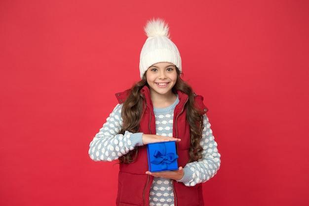冬休み。冬の衣装で幸せな子供は、ギフトボックスの赤い背景を保持します。ウィッシュリスト。ホリデーシーズン。幸せな子供時代。クリスマスプレゼント。休暇のお土産のコンセプト。女性への贈り物。クリスマスプレゼントのアイデア。