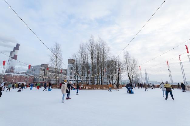 ロシアの冬休みとスケートリンクで楽しんでいる人々。