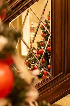 冬休みの室内装飾。食品のはしごの鏡に赤いつまらないものとお祝いのクリスマスツリー。新年のグリーティングカード。